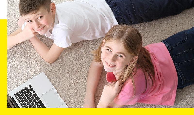 Rodzeństwo leżące przy laptopie