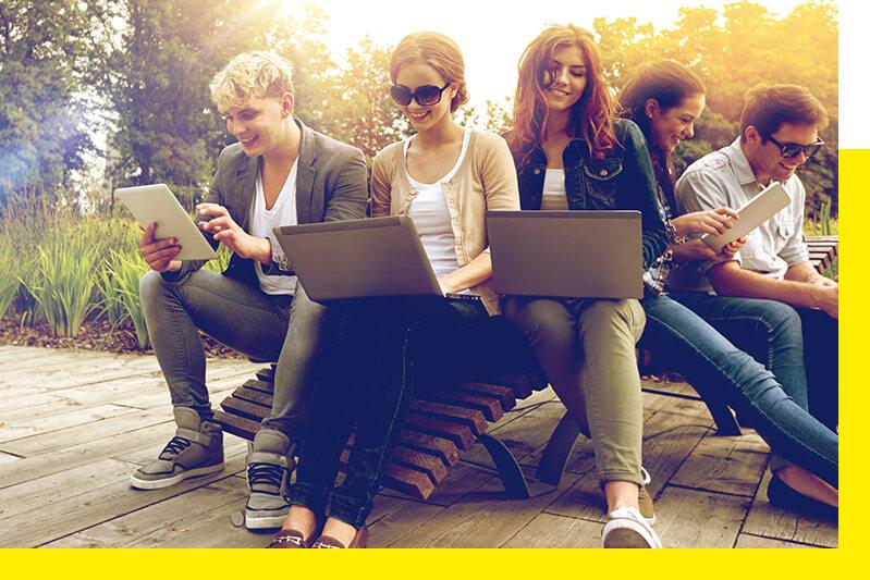 Grupa studentów ucząca się przy użyciu laptopów